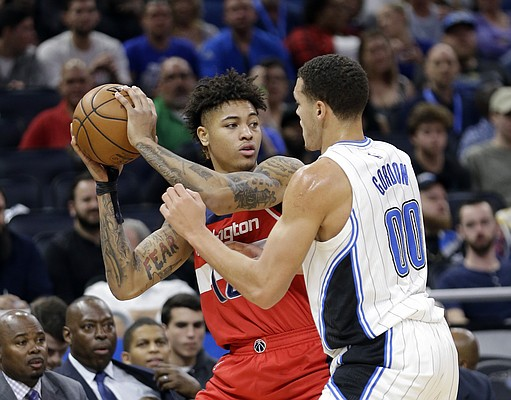 Washington Wizards' Kelly Oubre Jr., left, looks to pass the ball as he is defended by Orlando Magic's Aaron Gordon (00) during the first half of an NBA basketball game, Friday, Nov. 25, 2016, in Orlando, Fla. (AP Photo/John Raoux)