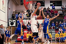 Lawrence High senior Kobe Buffalomeat (50) goes up for a reverse layup over Olathe South's Tre Adger (22) on Friday at LHS.