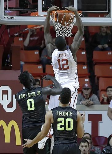 Oklahoma forward Khadeem Lattin (12) dunks as Baylor forward Jo Lual-Acuil Jr. (0) and guard Manu Lecomte (20) watch during the first half of an NCAA college basketball game in Norman, Okla., Friday, Dec. 30, 2016