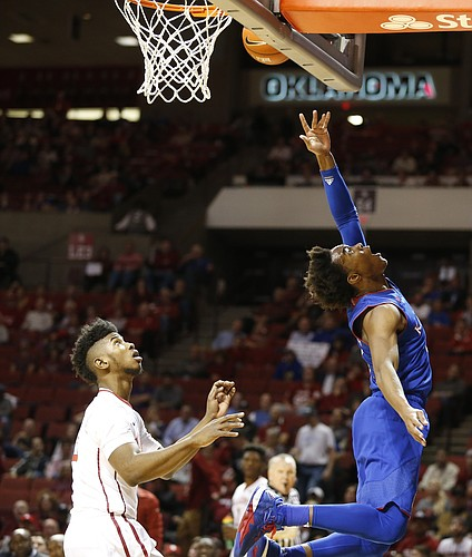 Kansas guard Devonte' Graham (4) gets a shot to drop before Oklahoma guard Christian James (3) during the first half, Tuesday, Jan. 10, 2017 at Lloyd Noble Center in Norman, Okla.