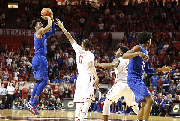 Kansas guard Devonte' Graham (4) pulls up for a three over Oklahoma guard Darrion Strong-Moore (0) during the first half, Tuesday, Jan. 10, 2017 at Lloyd Noble Center in Norman, Okla.