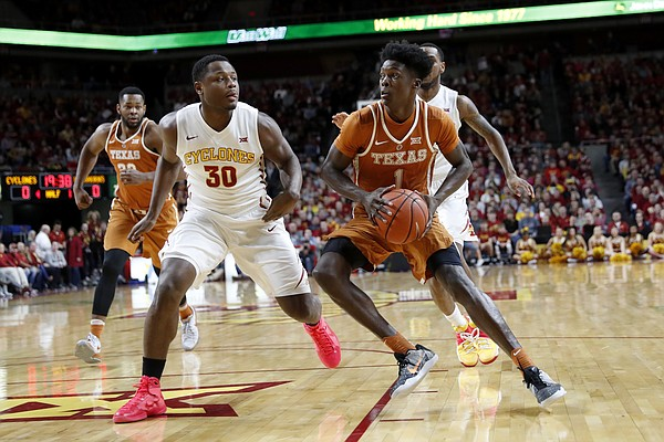 Texas guard Andrew Jones drives past Iowa State guard Deonte Burton, left, during the first half of an NCAA college basketball game, Saturday, Jan. 7, 2017, in Ames, Iowa.