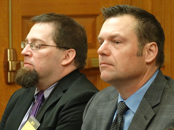 Secretary of State Kris Kobach, right, and Bryan Caskey, deputy secretary for elections, listen during a meeting of the Senate Ethics, Elections and Local Govenment Committee.