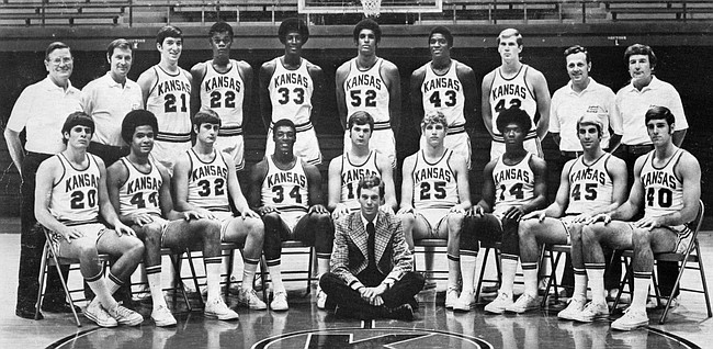 The 1973-1974 Kansas basketball team. Front row, from left: Paul Werner, Reuben Shelton, Dave Taynor, Nino Samuel, Jack Hollis, Bob Emery, Tommie Smith, Tom Kivisto and Dale Greenlee. Back row, from left: Dean Nesmith (trainer), Ted Owens (head coach), Roger Morningstar, Donnie Von Moore, Rick Suttle, Danny Knight, Norm Cook, Dale Haverman, Duncan Reid (assistant) and Sam Miranda (assistant). In front: Chuck Purdy (manager).