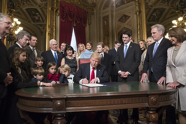 President Donald Trump is joined by the Congressional leadership and his family as he formally signs his cabinet nominations into law, Friday, Jan. 20, 2107, in the President's Room of the Senate on Capitol Hill in Washington From left are, Senate Majority Leader Mitch McConnell, R-Ky., Sen. Roy Blunt, R-Mo., Donald Trump Jr., Vice President Mike Pence, Jared Kushner, Karen Pence, Ivanka Trump, Melania Trump, Barron Trump, Speaker of the House Paul Ryan, R-Wis., Majority Leader Kevin McCarthy, D-Calif., House Minority Leader Nancy Pelosi, D-Calif. (AP Photo/J. Scott Applewhite, Pool)