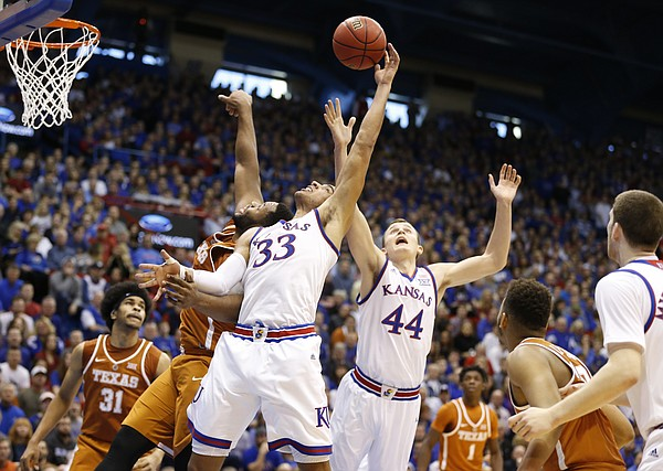 Kansas forward Landen Lucas (33) gets up for a rebound over Texas forward Shaquille Cleare (32) during the first half, Saturday, Jan. 21, 2017 at Allen Fieldhouse. At right is Kansas forward Mitch Lightfoot (44).