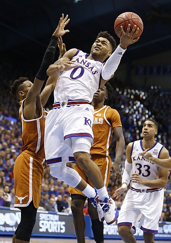 Kansas guard Frank Mason III (0) gets in for a bucket past Texas guard Kerwin Roach Jr., left, and Texas guard Andrew Jones during the second half, Saturday, Jan. 21, 2017 at Allen Fieldhouse.