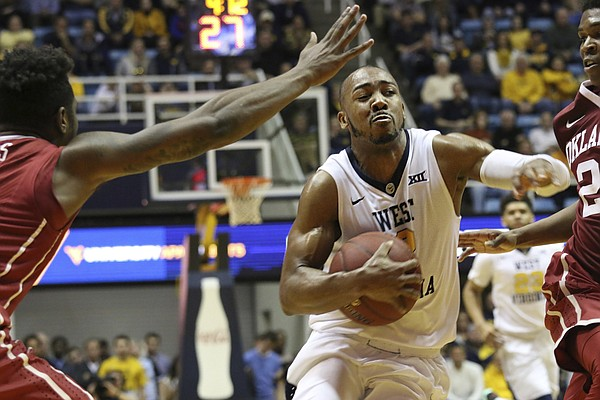 West Virginia guard Jevon Carter (2) breaks through Oklahoma players during the second half of an NCAA college basketball game, Wednesday, Jan. 18, 2017, in Morgantown, W.Va.