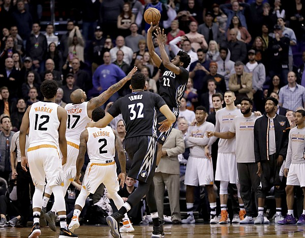 Minnesota Timberwolves forward Andrew Wiggins (22) shoots the game-winning basket as Phoenix Suns forward P.J. Tucker (17) defends during the second half of an NBA basketball game, Tuesday, Jan. 24, 2017, in Phoenix. The Timberwolves won 112-111. (AP Photo/Matt York)