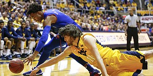Kansas guard Devonte' Graham (4) and West Virginia forward Nathan Adrian (11) compete for a loose ball during the first half, Tuesday, Jan. 24, 2017 at WVU Coliseum.