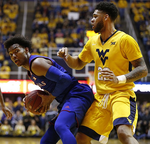 Kansas guard Devonte' Graham (4) looks to make a move on West Virginia forward Esa Ahmad (23) during the first half, Tuesday, Jan. 24, 2017 at WVU Coliseum.