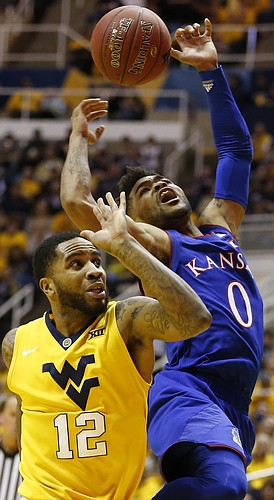 Kansas guard Frank Mason III (0) loses the ball on the drive against West Virginia guard Tarik Phillip (12) during the second half, Tuesday, Jan. 24, 2017 at WVU Coliseum.