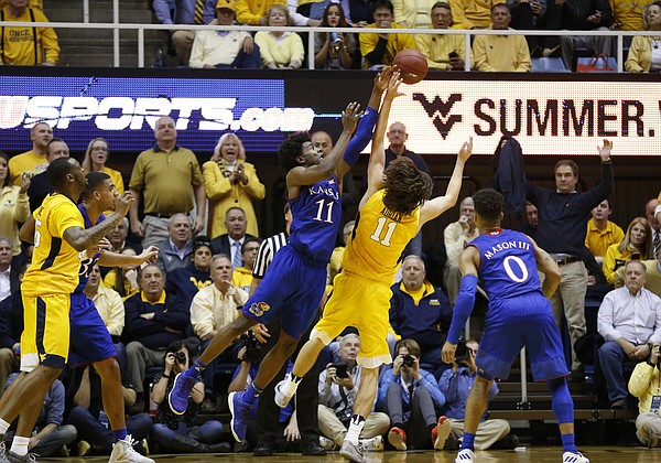 Kansas guard Josh Jackson (11) fights for a rebound with West Virginia forward Nathan Adrian (11) during the second half, Tuesday, Jan. 24, 2017 at WVU Coliseum.