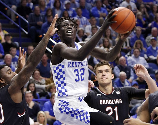 Kentucky's Wenyen Gabriel (32) shoots between South Carolina's Duane Notice, left, and Maik Kotsar during the first half of an NCAA college basketball game, Saturday, Jan. 21, 2017, in Lexington, Ky.