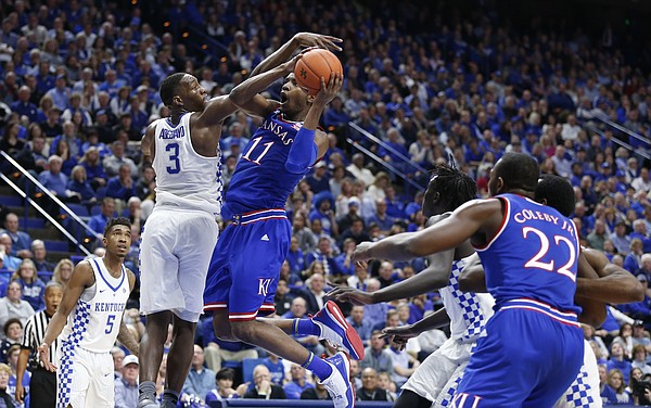 Kansas guard Josh Jackson (11) swoops under Kentucky forward Edrice Adebayo (3) for a bucket during the first half, Saturday, Jan. 28, 2017 at Rupp Arena in Lexington, Kentucky.