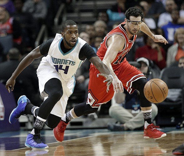 FILE — Former Chicago Bull Kirk Hinrich, right, and Charlotte Hornets' Michael Kidd-Gilchrist, left, chase a loose ball in the first half of an NBA basketball game in Charlotte, N.C., Monday, Feb. 8, 2016. (AP Photo/Chuck Burton)
