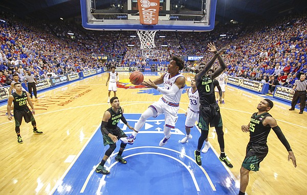 Kansas guard Devonte' Graham (4) swoops under Baylor forward Jo Lual-Acuil Jr. (0) for a bucket during the second half, Wednesday, Feb. 1, 2017 at Allen Fieldhouse.
