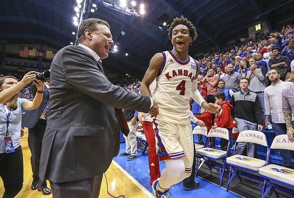 Kansas head coach Bill Self celebrates with Kansas guard Devonte' Graham (4) following the Jayhawks' 84-80 overtime win against West Virginia, Monday, Feb. 13, 2017 at Allen Fieldhouse.