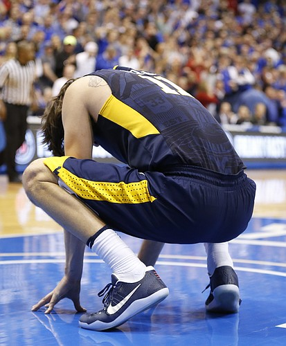 West Virginia forward Nathan Adrian (11) reacts after losing a ball off of his knee during overtime, Monday, Feb. 13, 2017 at Allen Fieldhouse.
