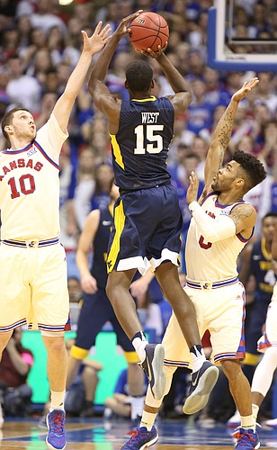 Kansas guard Sviatoslav Mykhailiuk (10) and Kansas guard Frank Mason III (0) defend against a three by West Virginia forward Lamont West (15) during the second half, Monday, Feb. 13, 2017 at Allen Fieldhouse.
