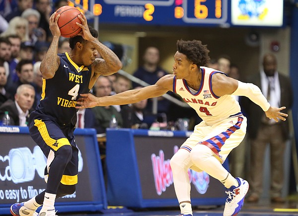 Kansas guard Devonte' Graham (4) defends against a drive by West Virginia guard Daxter Miles Jr. (4) during the second half, Monday, Feb. 13, 2017 at Allen Fieldhouse.