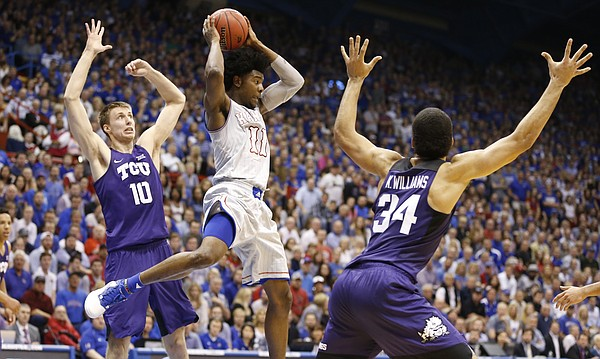 Kansas guard Josh Jackson (11) kicks out a pass beyond TCU forward Vladimir Brodziansky (10) and TCU guard Kenrich Williams (34) during the first half, Wednesday, Feb. 22, 2017 at Allen Fieldhouse.