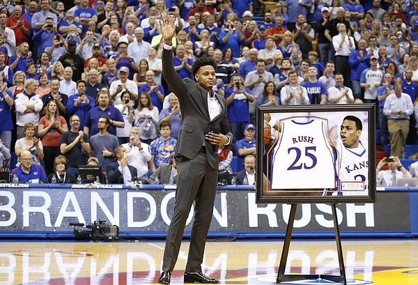 Former Kansas guard Brandon Rush waves to the crowd as his jersey is retired during a halftime ceremony.