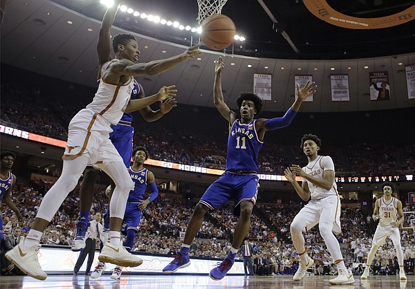 Texas guard Kerwin Roach Jr. (12) passes the ball as Kansas' Landen Lucas, left, and Josh Jackson (11) defend during the second half of an NCAA college basketball game, Saturday, Feb. 25, 2017, in Austin, Texas. Kansas won 77-67.