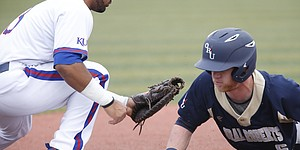 Kansas first baseman David Kyriacou (3) tries to nab Oral Roberts infielder Nick Roark (6) during a pickoff attempt in the first inning on Tuesday, Feb. 28, 2017.