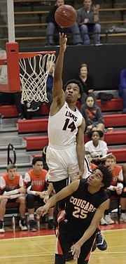 Lawrence High junior Anthony Selden (14) is fouled on a dunk attempt in a 6A sub-state win against Shawnee Mission Northwest, March 1, at LHS.