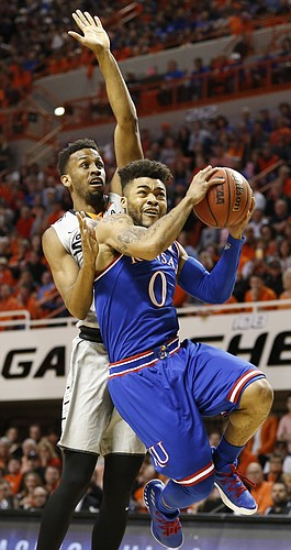 Kansas guard Frank Mason III (0) ducks under Oklahoma State forward Leyton Hammonds (23) for a shot during the first half, Saturday, March 4, 2017 at Gallagher-Iba Arena.