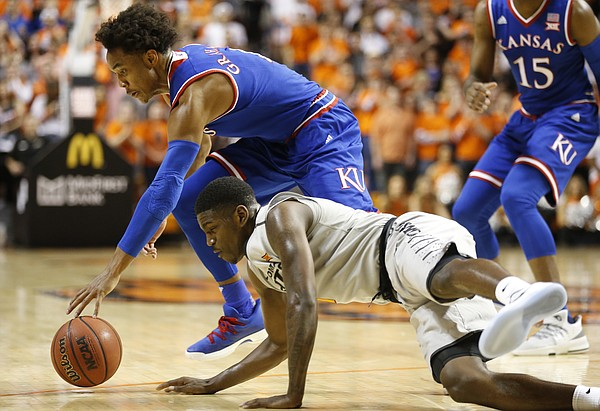 Kansas guard Devonte' Graham (4) and Oklahoma State guard Jawun Evans (1) fight for a loose ball during the first half, Saturday, March 4, 2017 at Gallagher-Iba Arena.