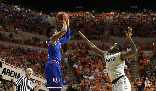 Kansas guard Devonte' Graham (4) pulls up for a three over Oklahoma State guard Jawun Evans (1) during the first half, Saturday, March 4, 2017 at Gallagher-Iba Arena.