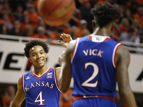 Kansas guard Devonte' Graham (4) comes in to slap hands  with Kansas guard Lagerald Vick (2) after an Oklahoma State foul during the second half, Saturday, March 4, 2017 at Gallagher-Iba Arena.
