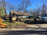 City of Lawrence employees clean up a downed silver maple tree Tuesday morning at 945 E. 10th St. The tree was knocked over by high winds during Monday night's storm.