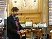 University of Kansas professor Ron Barrett-Gonzalez stands with a model of a drone missile being developed at KU, telling a legislative committee that it's one example of a research project soon to leave Kansas because of the state's expansive laws allowing people to carry concealed handguns on college campuses.