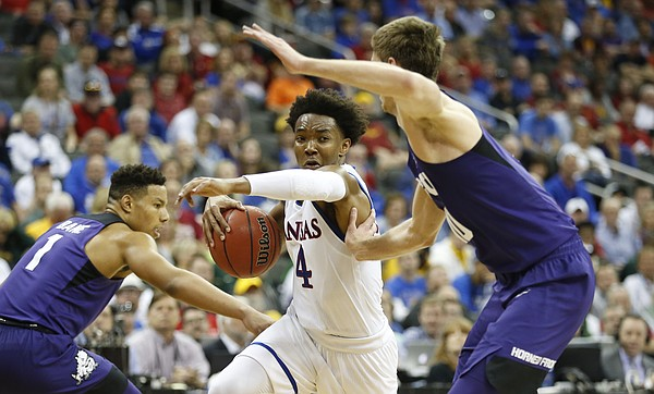 Kansas guard Devonte' Graham (4) tries to get around TCU forward Vladimir Brodziansky during the second half, Thursday, March 9, 2017 at Sprint Center. At right is TCU guard Desmond Bane (1).