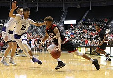Lawrence High sophomore guard Clarence King (24) dribbles past Blue Valley Northwest's Darien Jackson (25) on his way to the rim in the Class 6A state championship game at Koch Arena on Saturday, March 11. The Lions lost 64-61.