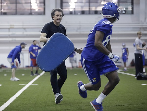 First-year Kansas offensive coordinator Doug Meacham puts KU receivers through workouts during the Jayhawks' first practice of the spring, on March 13, 2017, at Anschutz Pavilion.