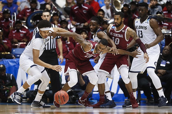 North Carolina Central's Pablo Rivas, center, and UC Davis' Garrison Goode, left, scramble for a wild ball during the second half of a First Four game of the NCAA men's college basketball tournament, Wednesday, March 15, 2017, in Dayton, Ohio. UC Davis won 67-63.