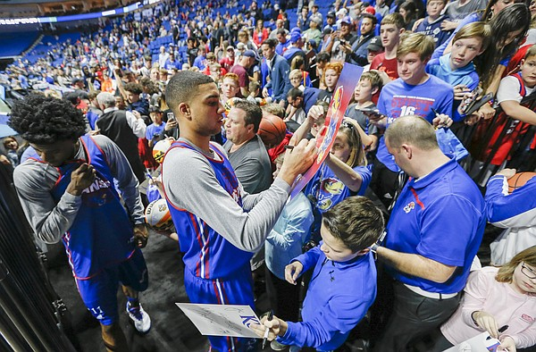 Kansas forward Landen Lucas signs a couple more autographs as the Jayhawks make their way from the court following a practice before fans on Thursday, March 16, 2017 at BOK Center in Tulsa, Oklahoma. At left is Kansas guard Josh Jackson.