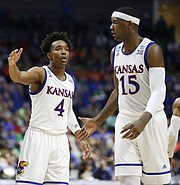 Kansas guard Devonte' Graham (4) slaps hands with Kansas forward Carlton Bragg Jr. (15) during the first half on Friday, March 17, 2017 at BOK Center in Tulsa, Oklahoma.