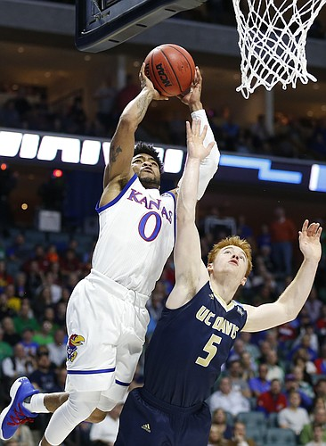 Kansas guard Frank Mason III (0) hangs to finish a bucket off a lob over UC Davis guard Siler Schneider (5) during the first half on Friday, March 17, 2017 at BOK Center in Tulsa, Oklahoma.