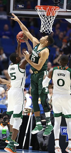 Michigan State forward Kenny Goins (25) gets up to defend against a shot by Miami center Ebuka Izundu (15) during the second half on Friday, March 17, 2017 at BOK Center in Tulsa, Oklahoma. At right is Miami guard Ja'Quan Newton (0).