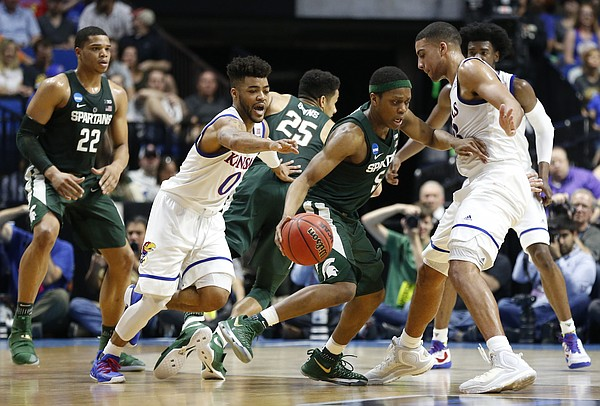 Kansas guard Frank Mason III (0) and Kansas forward Landen Lucas (33) defend Michigan State guard Cassius Winston (5) around the perimeter during the first half on Sunday, March 19, 2017 at BOK Center in Tulsa, Okla.