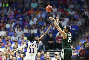 Michigan State guard Miles Bridges (22) puts up a three over Kansas guard Josh Jackson (11) during the first half on Sunday, March 19, 2017 at BOK Center in Tulsa, Okla.