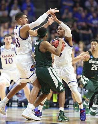 Kansas forward Landen Lucas (33) and Kansas guard Devonte' Graham (4) look to trap Michigan State guard Cassius Winston (5) during the first half on Sunday, March 19, 2017 at BOK Center in Tulsa, Okla.