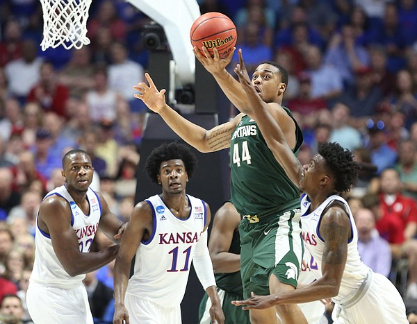 Kansas guard Lagerald Vick (2) fights for a rebound with Michigan State forward Nick Ward (44) during the second half on Sunday, March 19, 2017 at BOK Center in Tulsa, Okla.