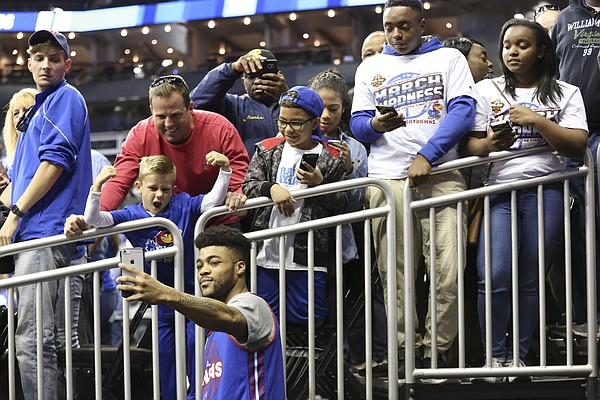 Kansas guard Frank Mason III (0) shoots a selfie with some Jayhawk fans awaiting autographs following the Jayhawks' practice on Wednesday at Sprint Center in Kansas City, Mo.