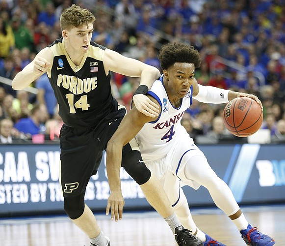 Kansas guard Devonte' Graham (4) drives against Purdue guard Ryan Cline (14) during the second half, Thursday, March 23, 2017 at Sprint Center in Kansas City, Mo.